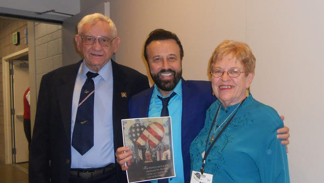 "Comiedian Yakov Smirnoff holds a picture of his 9/11 mural, ""America's Heart,"" and stands with Bob and Bobbie Gray of Mesa."