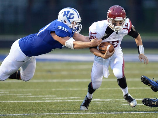 De Pere quarterback Emmett Kulick fights for yards as Notre Dame defensive lineman Blake Olejniczak brings him down during an August 2014 game.