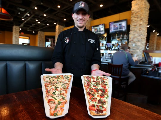Granite City chef Eric Gielau holds two flatbread pizzas, the pepperoni on the left and their signature maple bacon on the right.