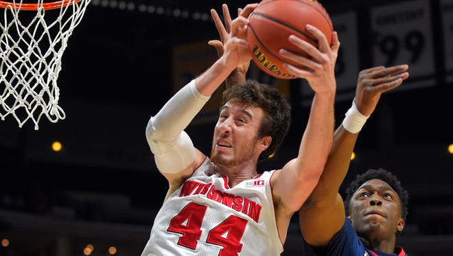 Wisconsin's Frank Kaminsky (44) grabs a rebound in front of Arizona's Stanley Johnson during the first half of a college basketball regional final in the NCAA Tournament, Saturday, March 28, 2015, in Los Angeles. (AP Photo/Mark J. Terrill)