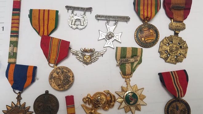 This collection of military decorations was found Friday in a police search of a Cedar Street house. Police seized items believed stolen from vehicles recently but some items, like the decorations, are not attributed.