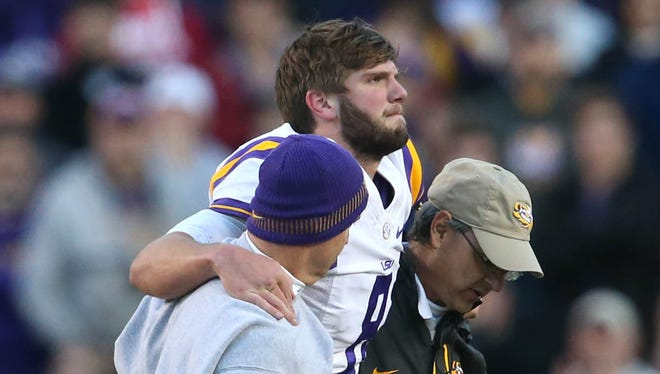 LSU quarterback Zach Mettenberger (8) is helped off the field after being injured in the fourth quarter against Arkansas on Friday at Tiger Stadium. LSU defeated Arkansas 31-27.