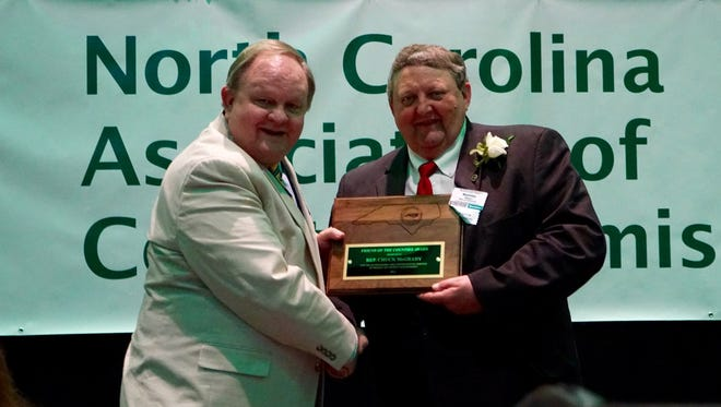 Rep. Chuck McGrady, R-Henderson, receives the 2015 Friend of the Counties Award from Macon County Commissioner Ronnie Beale, right.