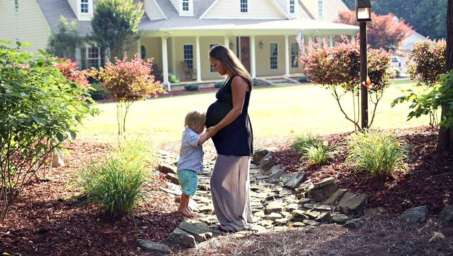 Talia Gates and her son, Kye, embrace her growing baby bump.
