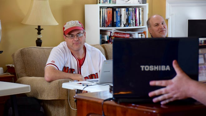 Patrick Hite bids for a player against fellow owner Brian Monroe, who participated via Skype from Vermont during their fantasy baseball league's annual draft in Staunton on April 2.