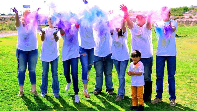 """Members of Luna County 4-H are shown playing with a sample batch of the powder to be used during the Powder to the People 5K color run on May 21, at Voiers """"Pit"""" Park."""
