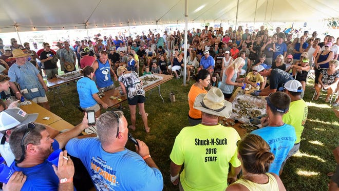 "Onlookers gather and cheer for competitors in the ""Shuck-n-Suck"" oyster eating contest during the 12th Annual Oyster Buy Boat Reunion and Shuck-N-Suck event hosted by the The Oyster Farm Marina & Vacation Rentals on August 6, 2016."