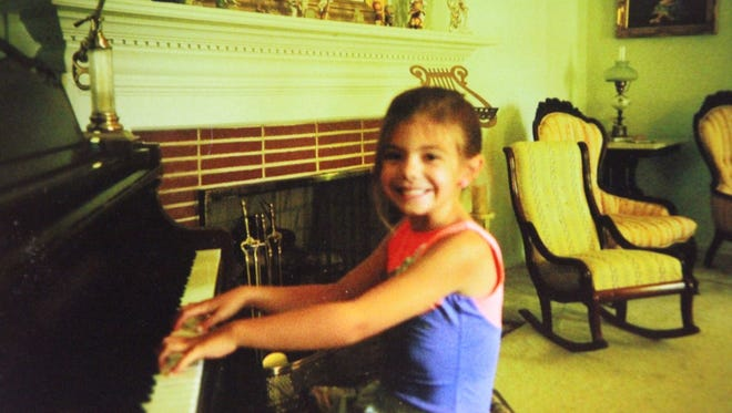 Harmony Bates poses for a picture while playing piano.