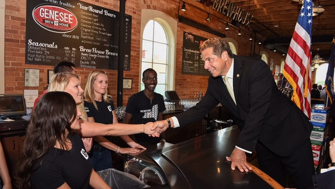 Gov. Andrew Cuomo, right, greets the staff of the Genesee Brew House Wednesday, Sept. 7, 2016, before signing a bill that allows alcohol sales at 10 a.m. on Sundays.