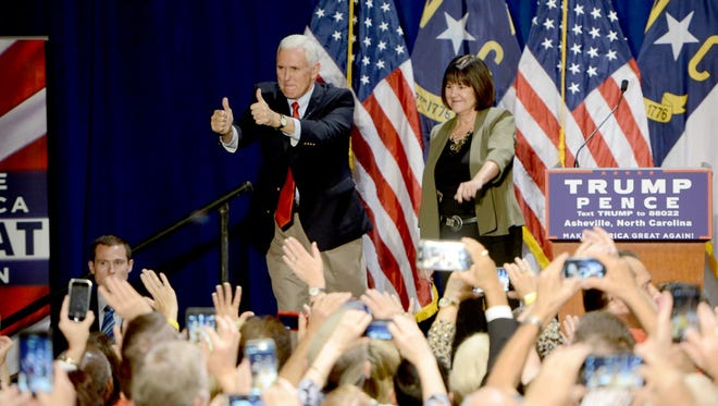 Gov. Mike Pence and his wife, Karen, take to the stage at the WNC Ag Center in Fletcher during a rally for the Trump/Pence campaign on Monday, Oct. 10, 2016.