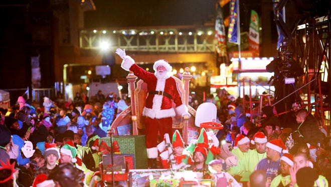 Santa makes his way through the crowd in the Lots of Lights Parade in downtown Louisville.  November 25, 2016