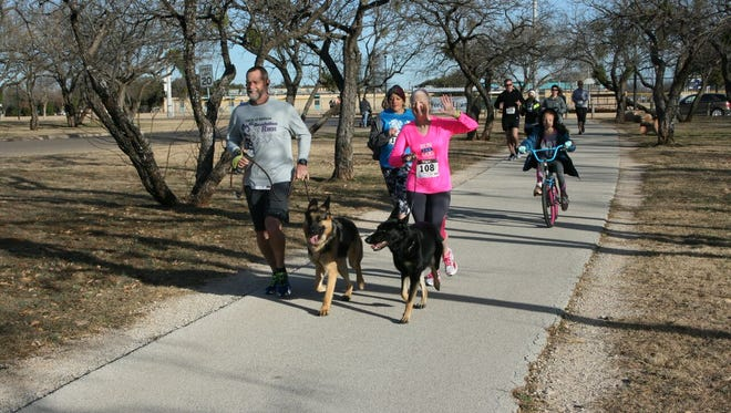 Dogs and their owners were part of a group of more than 100 to participate in the YMCA's sixth annual Resolution Run on Saturday at Redbud Park.