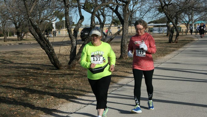 Louise Cannon, left, makes her way around the 5-kilometer course for the YMCA's sixth annual Resolution Run on Saturday at Redbud Park. This was Cannon's first year to participate in the Run.
