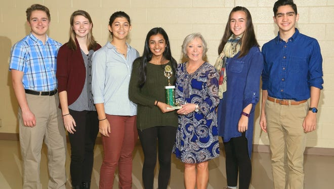 Lyndi Bonnette, fifth from the left, SCISA activities director, is shown presenting the second-place trophy to Montessori School of Anderson students, from left, Jack Hill, Morgan Merriman, Zayna Sheikh, Sakshi Joglekar, Emma Rogers and William Joseph they won during the SCISA High School Math Meet.