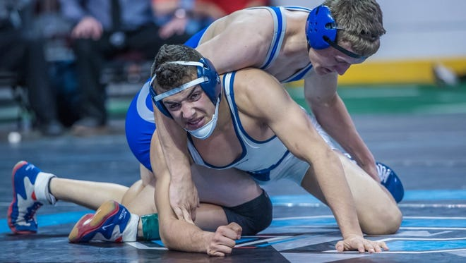 Piedra Vista's Nick Rino, bottom, looks to escape from Carlsbad's Justin Wood during the 6A 145-pound title match on Saturday at the Santa Ana Star Center in Rio Rancho.