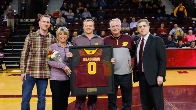 Holt grad and Central Michigan men's basketball senior Tanner Beachnau takes a photo with his brother, Taylor (far left), mother, Carmen (second to left), father, Dana (second to right), and coach Keno Davis (far right) on Feb. 28 during the Chippewas' senior night. Beachnau was a walk-on who didn't play his last two years after suffering two separate ACL tears.