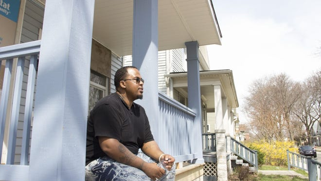 Theodore Miles sits on the front steps of his future home that he built with Habitat for Humanity.