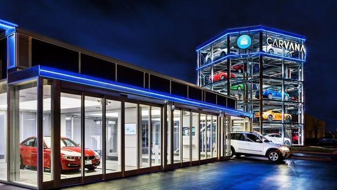 """Carvana buyers use a special coin to retrieve their vehicle from the company's """"vending machine"""" near Nashville."""