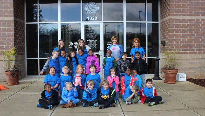 Calhoun Academy of the Arts first-grade teacher Katie Laughridge is shown with her first-grade class and staff members as they pose together for keepsake.