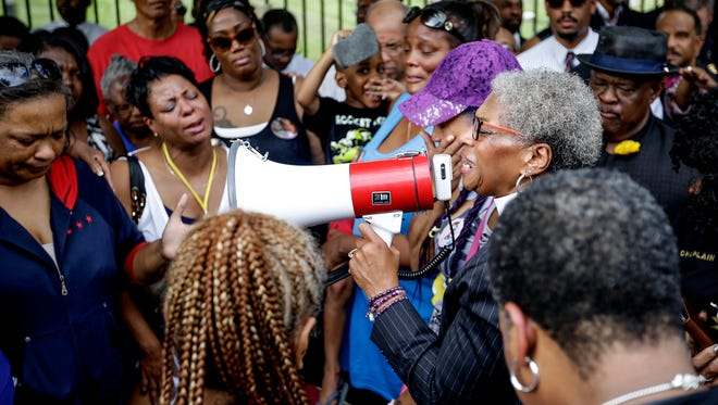 Anne Henning Byfield, Bishop of AME Church, leads a prayer for women during a calling for peace at Sutherland Park Cemetery on Wednesday, July 26, 2017.