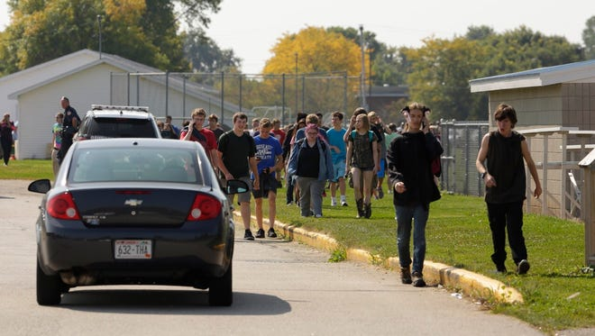 Oshkosh West High School students evacuate the building Thursday after a bomb threat at the school.