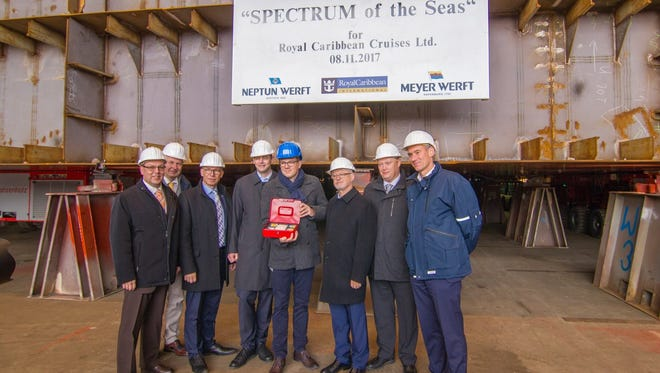 Executives from Royal Caribbean and the Neptun Werft shipyard pose for a photo at a keel-laying ceremony for Royal Caribbean's Spectrum of the Seas.