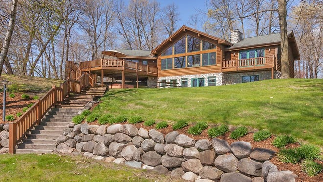 . A wide gradual stone staircase descends past the quaint rock landscaping to the 160-foot stretch of private shoreline.
