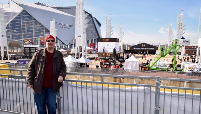 Bill Jahn poses outside the Mercedes-Benz Stadium in Atlanta before the college football national title game.