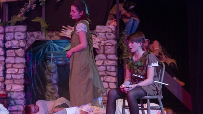 Wendy Darling (left) , played by Elizabeth Bocksenbaum, and Peter Pan (right), is played by Mary Wells. A group playing the Lost Boys who are seen sleeping are in the foreground while the sleeping natives  are in the background.      