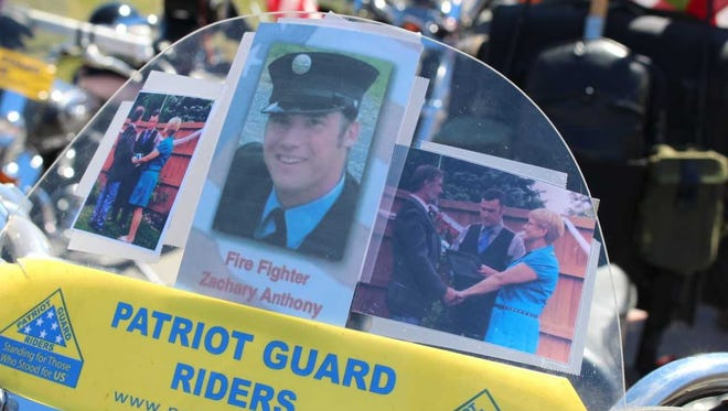 A memorial for Zachary Anthony on Patriot Guard Rider Craig Fussell's motorcycle features pictures of Fussell's wedding, which Anthony officiated.