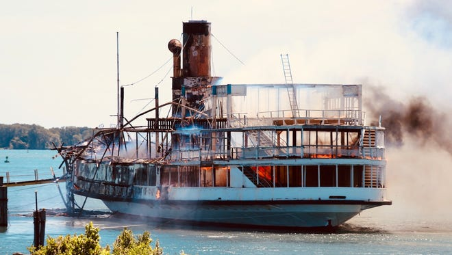 The Boblo boat catches fire at the Riverside Marina in Detroit on Friday, July 6, 2018, while the Curtis Randolph fireboat from the Detroit fire department puts out the flames.