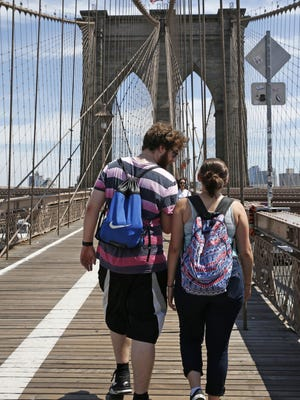 A couple walks across the Brooklyn Bridge in New York, one of the city's best free experiences.