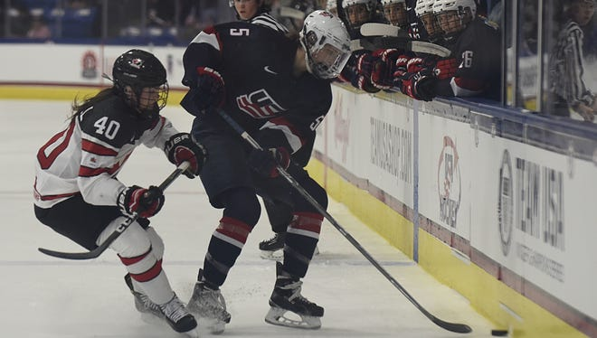 Farmington's Megan Keller (right), is shown playing for the U.S. Women's National Team during a December exhibition game. Keller and teammates reportedly will boycott the 2017 IIHF Women's World Championship in Plymouth unless there is progress in contract talks with USA Hockey.