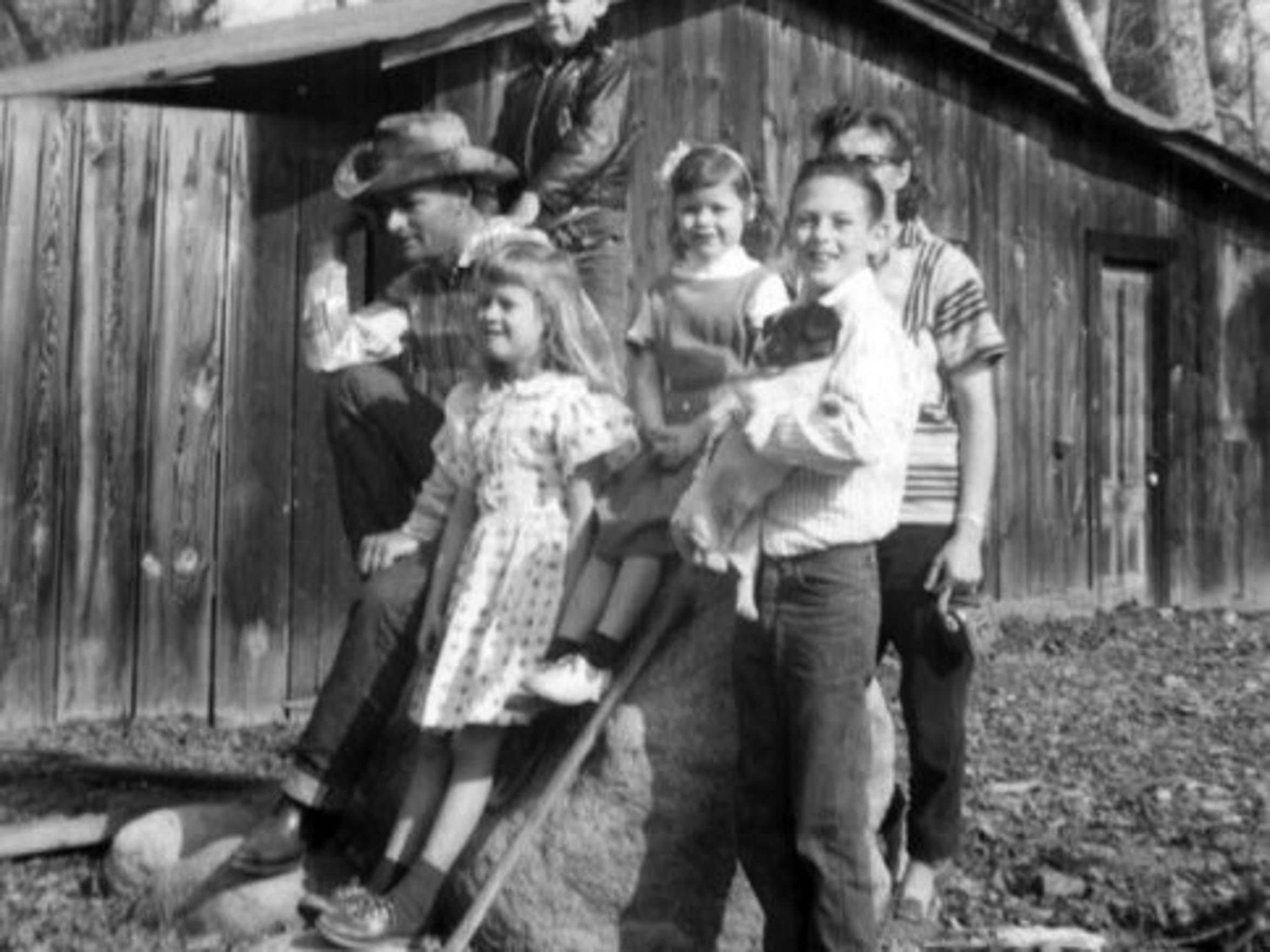 "Ron Hughart, at right holding a dog, is pictured as a boy with his parents and three of his four siblings. They lived an Okie life, that is, they followed work around California, relocating up to three times a year to follow the fruit, milk cows or drive tractors. Although he was once labeled retarded in the second grade, he grew up to become a teacher and worked in law enforcement, retiring as the assistant police chief in Woodlake. He also wrote two award-winning books, ""The Place Beyond the Dust Bowl"" and ""Beyond the Dust Bowl with a Pocket Full of Peanuts."""