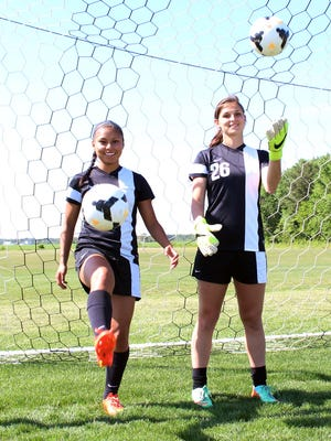 The Sussex Tech girls soccer team's senior captains couldn't be more different. Michelle Laz, left, scores goals while Leslie Fazio stops them. They're at different ends of field, but they happen to be best friends.