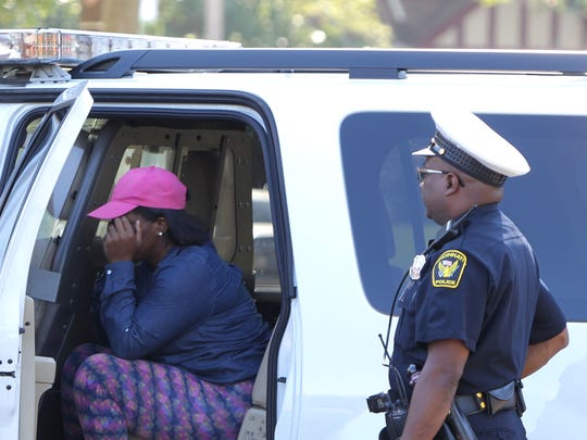 A woman police were questioning at the scene of a shooting in College Hill sits in a police SUV during a break in the questioning.