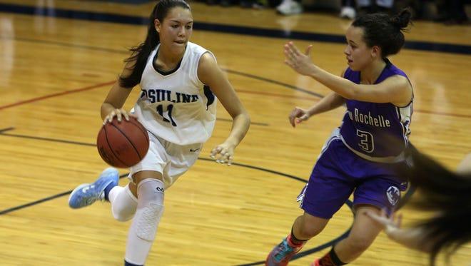 Ursuline's Korina Guerra drives past New Rochelle's Kayla Correa in a girls basketball game at Ursuline High School in New Rochelle Jan. 21, 2015.