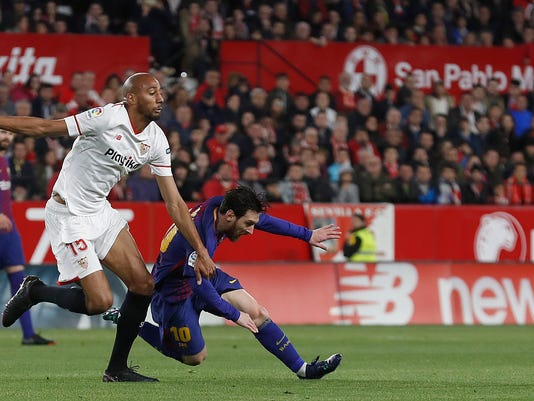 Barcelona's Messi, right, and Sevilla's N'zonzi fight for the ball Sevilla during La Liga soccer match between Barcelona and Sevilla at the Sanchez Pizjuan stadium, in Seville, Spain on Saturday, March 31, 2018. (AP Photo/Miguel Morenatti)
