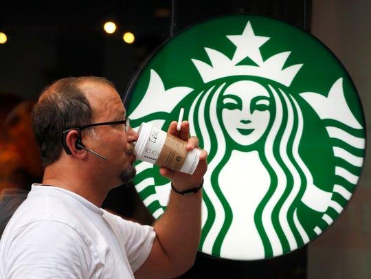 A man drinks a Starbucks coffee in New York.