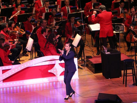 Salonga sports a tuxedo and a pixie haircut while performing
