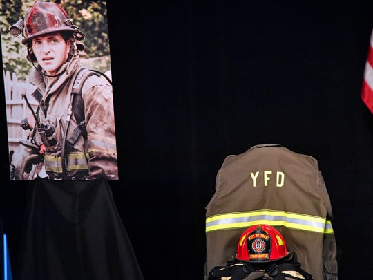 Ivan Flanscha's helmet and turnout gear are displayed onstage at a public memorial service.