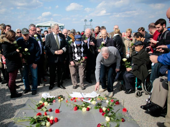 Buchenwald survivor Henry Oster, center right, and veteran medic James E. Anderson, center, who was with the U.S. liberation troops, lay down flowers with other veterans prior to a minute of silence at 15:15 in the afternoon to mark the 70th anniversary of the liberation of the former Nazi concentration camp Buchenwald near Weimar, Germany.