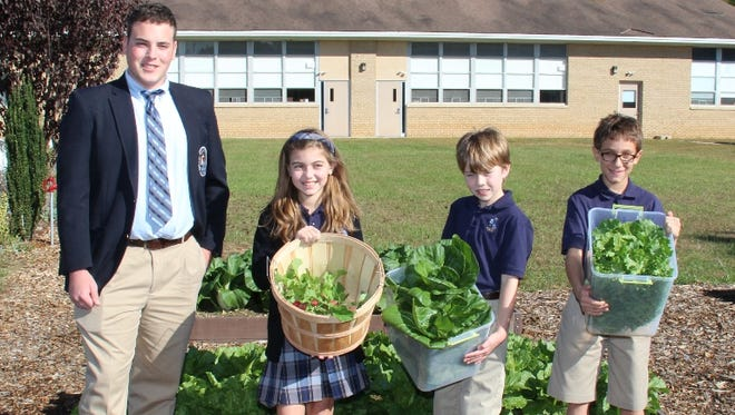 (From left) Daniel Biagi, a senior at St. Augustine College Preparatory School, and St. Mary School fifth-graders Avery Dortu, Connor Allen and Douglas Farinaccio harvested vegetables from the garden that Biagi built for his Caritas Project.