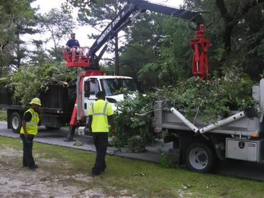 City and county workers clean storm debris near the