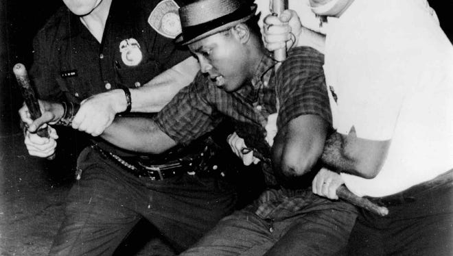 Apprehended - Police officers struggle with man here as they take him into custody during disturbances. New clashes flared for the second night in a row in Rochester. (AP photo, 7/25/1964)