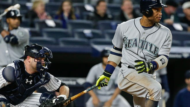 Seattle Mariners' Robinson Cano follows through on an RBI single during the fourth inning of a baseball game as New York Yankees catcher Brian McCann watches, Friday, April 15, 2016, in New York.