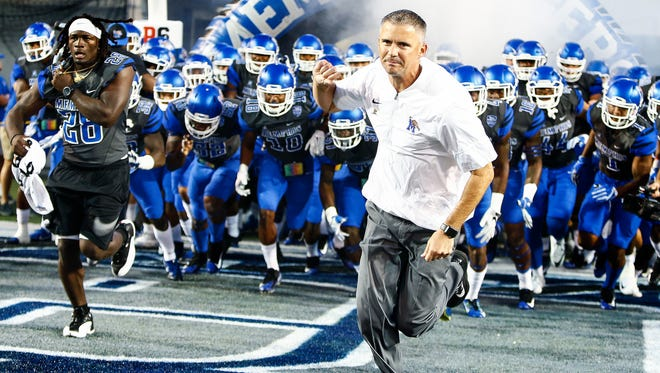 Memphis coach Mike Norvell (right) leads his team onto the field before taking on Southern Illinois on Sept. 23, 2017, at Liberty Bowl Memorial Stadium.