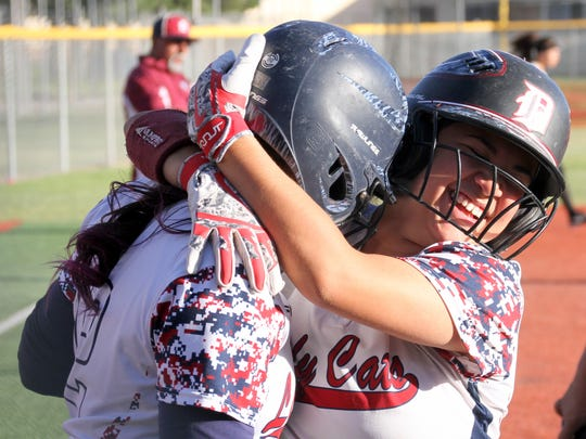 Jessalynn Olivas hugs Aileen Jacquez after Jacquez belted a two-run home run in Deming High's 18-0 rout over the visiting Chaparral High Lobos on Friday.