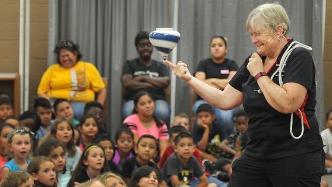 World Top Spinner Female Champion and Minnesota State Yo-Yo Champion Val Oliver demonstrates the science of motion Wednesday using a large wooden top to a group of school aged kids during the Wichita Falls Public Library's the Science of Spin class.