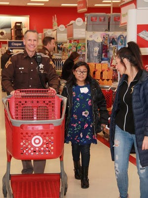 A sheriff's deputy shops with an underprivileged child at Target in Fishers on Dec. 9, 2017.